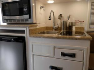 Kitchen Galley with Fridge, Microwave, Sink and Stove Top Burners